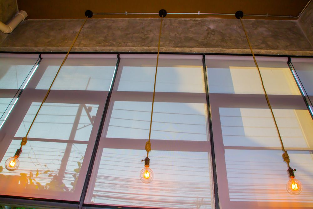 commercial drop down blinds behind retro hanging light bulbs