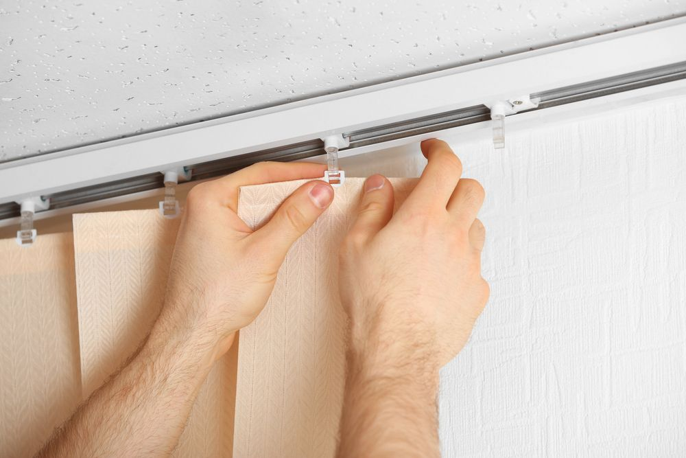 Male hands installing vertical blinds