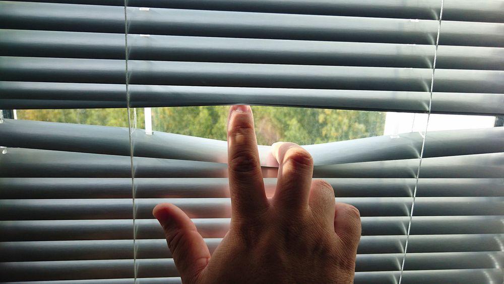 Man's hand revealing white venetian blinds.Hand Opening slats of Venetian blinds with a finger